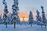 Orange Sky at Sunset Over Snow-covered Evergreens and a Tee Pee Form Fotografisk tryk af Mike Theiss