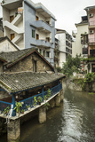 A Restaurant and Apartments Rise Above a River in Yangshuo, China Photographic Print by Jonathan Kingston