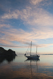 A Sailboat Anchored in a Bay During a Colorful Sunset Photographic Print by James Forte