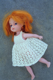 Modern Girl Doll with White Knitted Dress And Ginger Hair Lying On Her Side On Grey Slate Photographic Print by Den Reader
