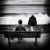 Elderly Couple Watch the Waves Photographic Print by Rory Garforth