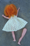 Girl Doll with White Knitted Dress And Ginger Hair Lying Face Down On Grey Slate Photographic Print by Den Reader