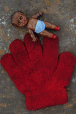 Grubby Red Woollen Childs Glove Lying On Rusty Metal Sheet with Small Plastic Doll of Black Child Photographic Print by Den Reader