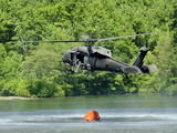 A UH-60 Blackhawk Helicopter Fills a Suspended Water Bucket in Marquette Lake, Pennsylvania Photographic Print by Stocktrek Images