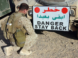 Soldier Secures a Warning Sign To the Front of His Humvee Photographic Print by Stocktrek Images