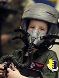 A Young Boy Wears a Helmet with Oxygen Mask Attached Photographic Print by Stocktrek Images
