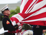A United States Marine Takes the American Flag Into His Hands Before Folding It Photographic Print by Stocktrek Images