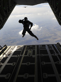 A Paratrooper Salutes As He Jumps Out of a C-130J Super Hercules Photographic Print by Stocktrek Images