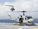 A UH-1N Huey And An AH-1W Super Cobra Land On Flight Deck of USS Essex Photographic Print by Stocktrek Images