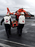 Personnel Carry An Injured Sailor To a Coast Guard MH-65 Dolphin Helicopter Photographic Print by Stocktrek Images