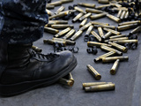 Shell Casings from a .50 Caliber Machine Gun Around the Feet of a Soldier Photographic Print by Stocktrek Images