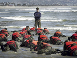 A Navy SEAL Instructor Assists Students During a Hell Week Surf Drill Evolution Photographic Print by Stocktrek Images