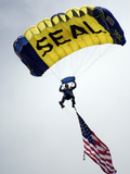 A Member of the U.S. Navy Parachute Team Descend Through the Sky with the American Flag Photographic Print by Stocktrek Images
