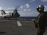 A Crew Chief Watches a CH-46E Sea Knight Helicopter Aboard USS Makin Island Photographic Print by Stocktrek Images
