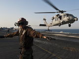 Airman Checks For a Clear Deck As An MH-60S Sea Hawk Takes Off USS John C. Stennis Photographic Print by Stocktrek Images