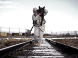 A Military Dog Handler Uses An Over-the-shoulder Technique To Carry His Dog Photographic Print by Stocktrek Images