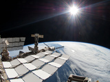 The Bright Sun, a Portion of the International Space Station And Earth's Horizon Photographic Print by Stocktrek Images