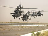 A Group of AH-64D Apache Helicopters Landing On the Runway Photographic Print by Stocktrek Images