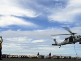 An MH-60S Sea Hawk Lifts a Pallet of Ordnance from the Aircraft Carrier USS Ronald Reagan Photographic Print by Stocktrek Images