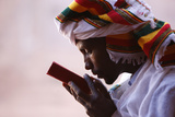 Faithful Kissing a Bible Outside a Church in Lalibela Photographic Print