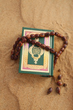 Coran and Prayer Beads in Sand Photographic Print