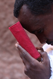 Faithful Holding a Bible Outside a Church in Lalibela Photographic Print