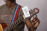 Young Christian Man Tuning a Guitar Photographic Print