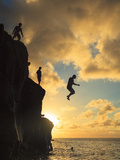 USA, Hawaii, Oahu,  North Shore, Waimea Bay, Divers Jumping Off Cliff Photographic Print by Michele Falzone