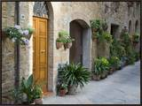 Flower Pots and Potted Plants Decorate a Narrow Street in Tuscan Village, Pienza, Italy Framed Canvas Print by Dennis Flaherty