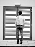 A Young Man Standing in the Street Looking at a Pair of Doors Metal Print by India Hobson