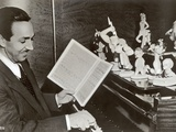 Walt Disney Plays Piano to a Group of Figures of Disney Characters, c.1940 Photographic Print by  German photographer