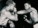 Young Cassius Clay Scores with a Left Against the Veteran Archie Moore in the First Round of the… Photographic Print by  American Photographer