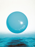 Blue Sphere with Reflection of Sun Floating Over Sea Photographic Print by Green Light Collection