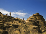 Walkers on Rocks Showing Effects of Water Erosion Photographic Print by Green Light Collection