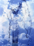 Slow Motion Geyser of Water Rising Through Blue Sky And Clouds Photographic Print by Green Light Collection