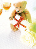 Teddy Bear, Gift Pack, Drinking Glass And Yellow Rose on Table Top Photographic Print by Green Light Collection