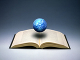 Small Cloud Filled Globe Hovering Above Open Book Photographic Print by Green Light Collection