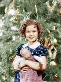 Shirley Temple holding doll by Christmas tree, ca. late 1930s Posters