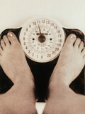 Woman's Feet on a Set of Weighing Scales Photographic Print by  Cristina