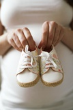 Pregnant Woman Holding Baby Shoes Photographic Print by Ian Boddy