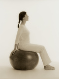 Woman Sitting on Exercise Ball Photographic Print by  Cristina