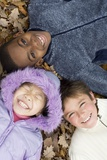 Smiling Children Lying on Autumn Leaves Photographic Print by Ian Boddy