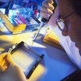 Technician Using a Pipettor During DNA Sequencing Photographic Print by Tek Image