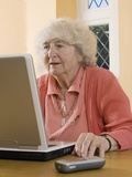 Elderly Woman Using a Laptop Computer Photographic Print by Steve Horrell