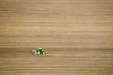 Tractor Ploughing a Field Prints