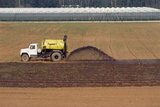 A Tractor Spreading Pig Manure on a Field Photographic Print by David Nunuk