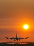 Aeroplane Landing At Sunset Photographic Print by David Nunuk