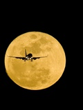 Aeroplane Silhouetted Against a Full Moon Photographic Print by David Nunuk