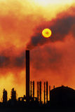 Smoking Chimneys of An Oil Refinery At Sunset Photographic Print by David Nunuk