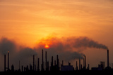 Smoking Chimneys of An Oil Refinery At Sunset Posters by David Nunuk